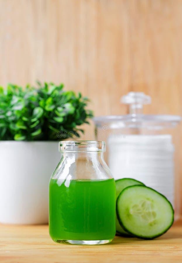 Cucumber juice in a small glass jar for preparing natural facial toner. Homemade cosmetics. stock image