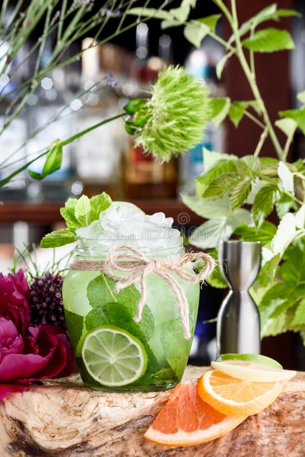 Cucumber lemonade with ice and slices of cucumber and lime in beautiful round glass on the background of fresh flowers royalty free stock images