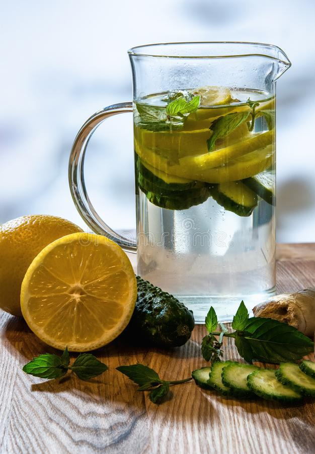 Cucumber mint ginger and lemon detox water with ingredients on wooden table. royalty free stock images