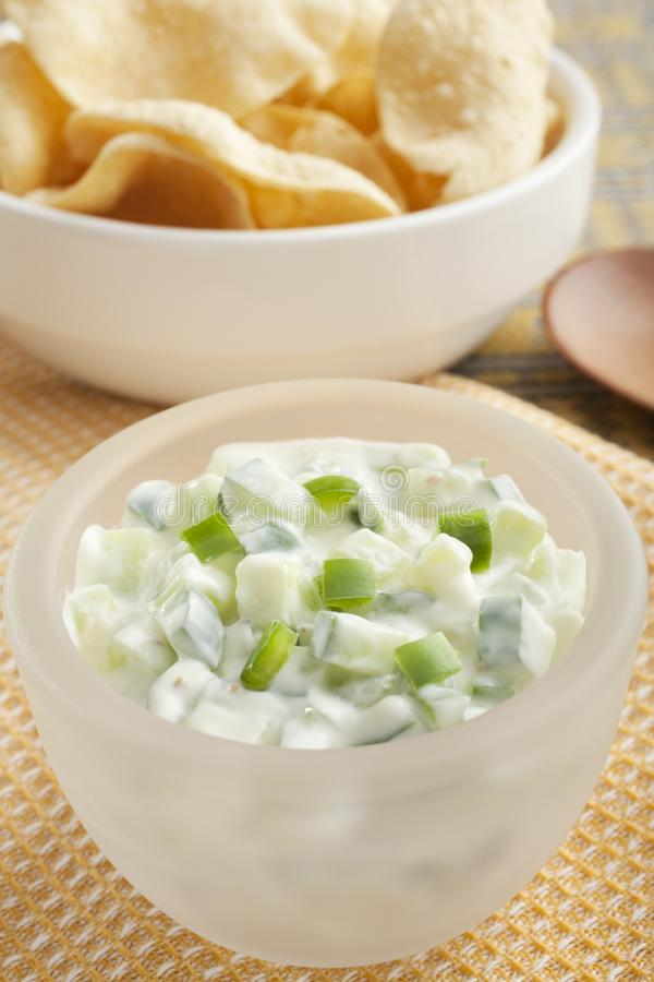 Cucumber Raita Indian Accompaniment with Mini Pappadums. Indian curry accompaniment cucumber raita, made from yoghurt, cucumber, green chili, roasted ground royalty free stock images