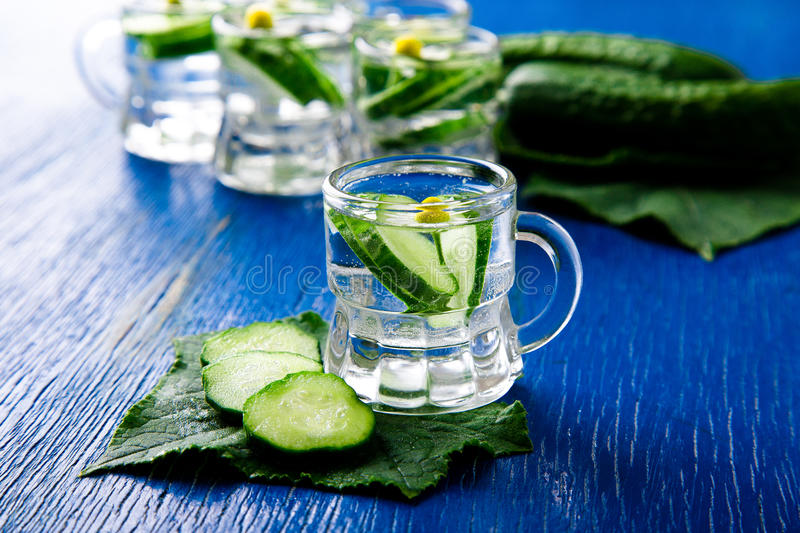Cucumber water in little mason glass jar on blue background. Rustic. royalty free stock photo