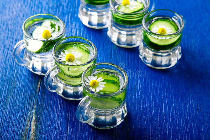 Cucumber water in six little mason glass jar on blue background. Rustic. Detox stock photography