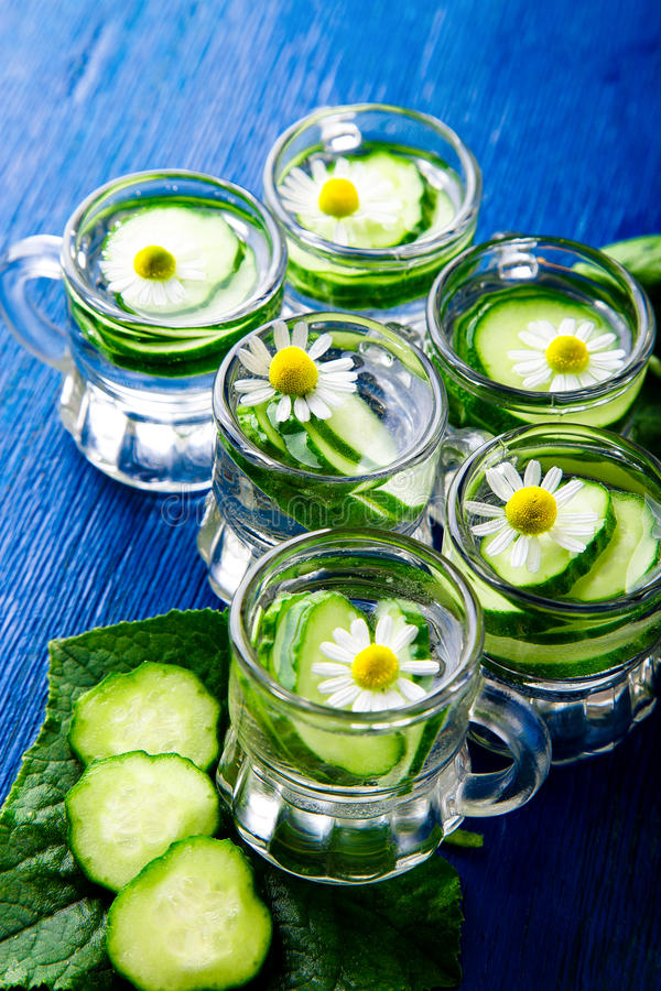 Cucumber water in six little mason glass jar on blue background. Rustic. Detox royalty free stock photo