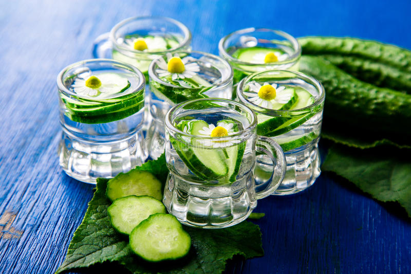 Cucumber water in six little mason glass jar on blue background. Rustic. Detox royalty free stock image