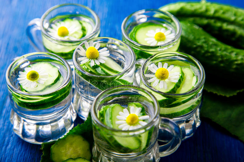 Cucumber water in six little mason glass jar on blue background. Rustic. Detox royalty free stock images