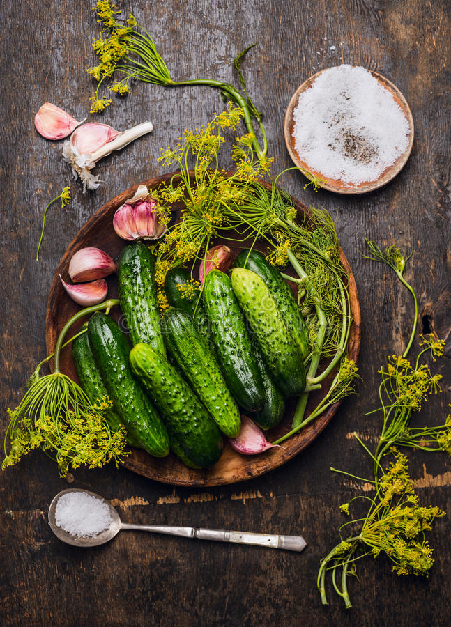 Cucumbers, herbs and spices for pickling on rustic wooden background. Top view royalty free stock photo
