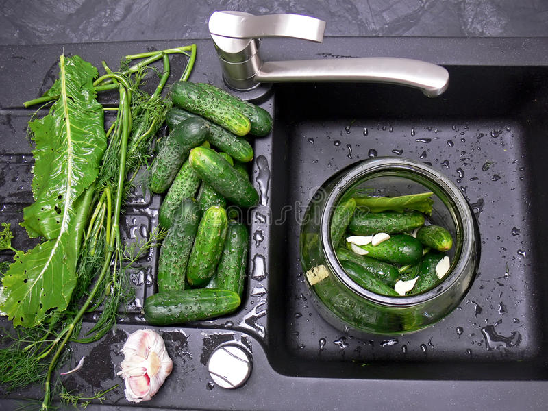 Cucumbers pickling. Top view of the home-made process of cucumbers pickling. The black sink with the washed cucumbers and other ingredients stock photo