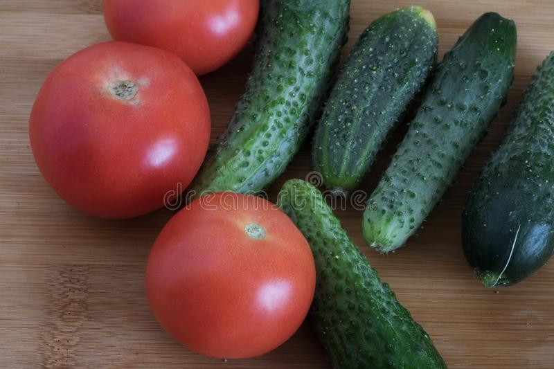 Cucumbers and tomatoes close-up on a wooden background, summer vegetables, harvest, salad preparation royalty free stock photography