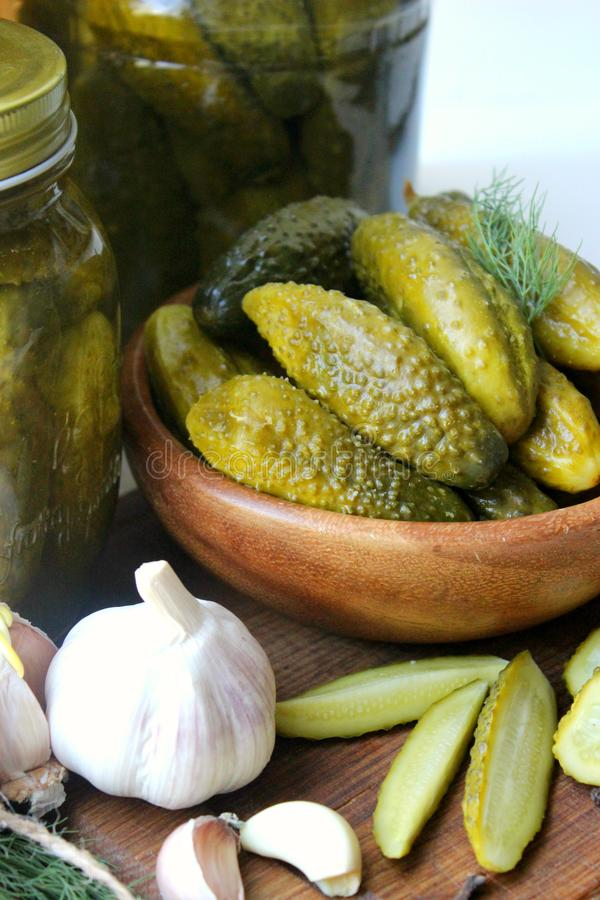 Cucumbers in a wooden bowl, spices for pickling and jars of pickled cucumbers on the table royalty free stock photo