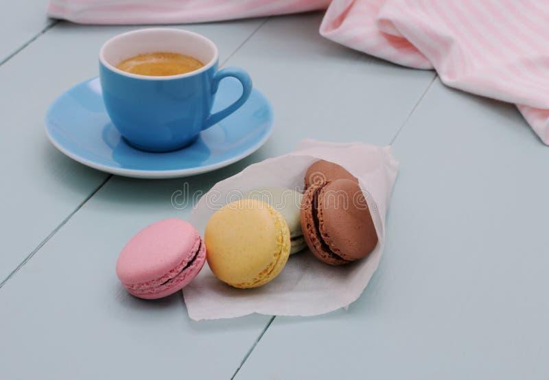Cucurucho del papel de trazo con los macarons y la taza azul del café express imagenes de archivo