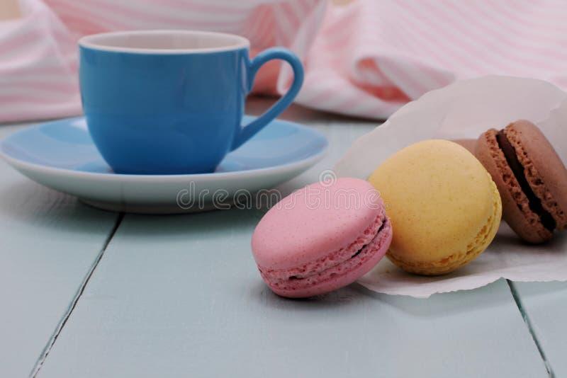 Cucurucho del papel de trazo con los macarons y la taza azul del café express fotos de archivo libres de regalías