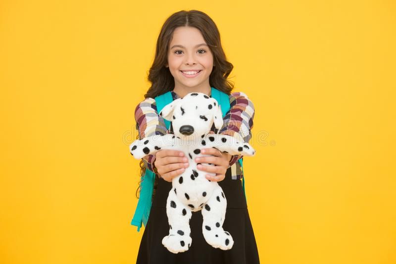 Cuddly dog. Happy small girl hold toy dog yellow background. Little schoolchild smile with soft dog. Adorable dog pet. Gift. Early learning. Friends and stock photos