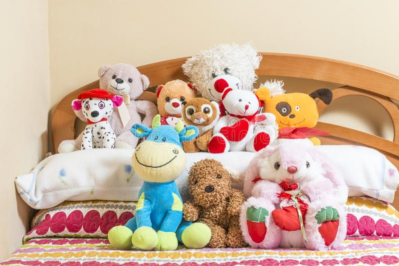 Cuddly toys on a bed. A lot of cuddly toys on top of a bed stock images