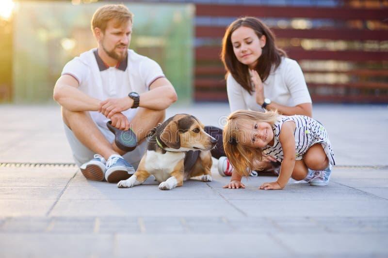 Cudowna młoda rodzina jest odpoczynkowym obsiadaniem na ziemi zdjęcia stock