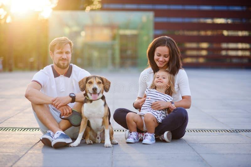 Cudowna młoda rodzina jest odpoczynkowym obsiadaniem na ziemi fotografia royalty free