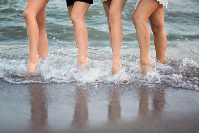 Cudowne długonogie kobiety chodzą blisko morza na piasku S sport kobiet ` śliczne nogi fotografia stock