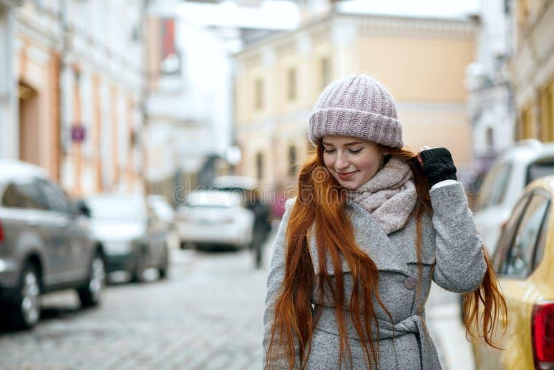Cudownej czerwieni głowy zimy wzorcowa jest ubranym nakrętka i żakiet pwalking przy zdjęcia stock