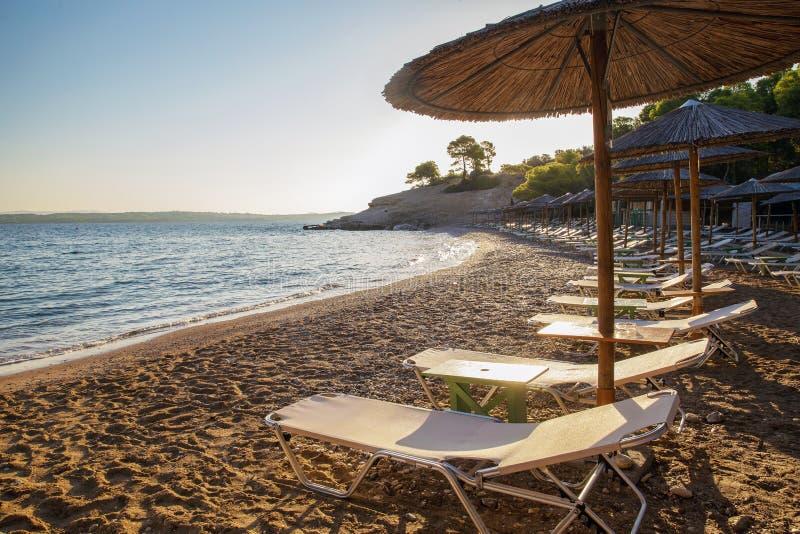 Cudowny Grecja - plaża: przejrzysta woda piaska i słomy markizy obraz stock