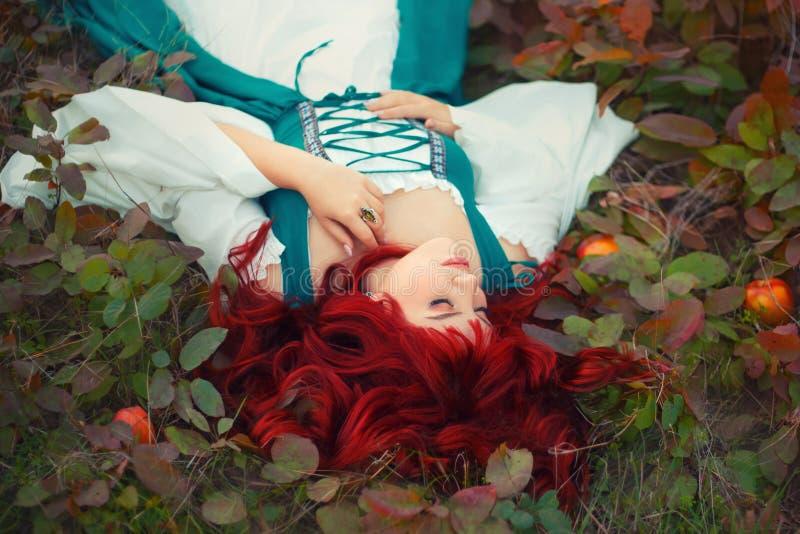 Cudowny miedzianowłosy princess kłama na ziemi, drzejącej z liśćmi, delikatnie kłaść jej rękę, ubierającą w długim szmaragdzie obrazy royalty free