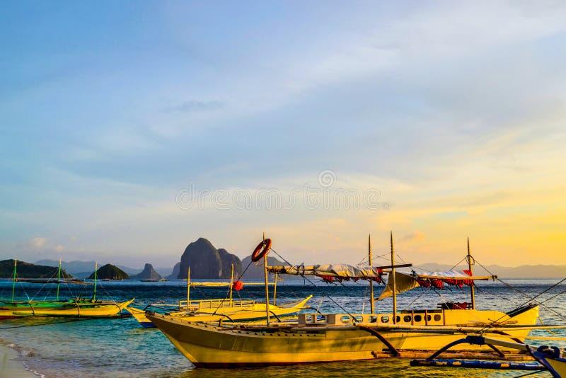 Cudowny widok zmierzchu nieba migocące denne falezy na horyzoncie i łodziach cumował obok piaskowatej plaży zdjęcie royalty free