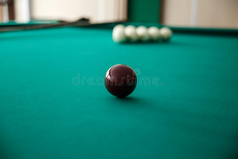 Cue ball for Russian billiards on the table. White billiard balls on the background. Green cloth. Selective focus stock photos