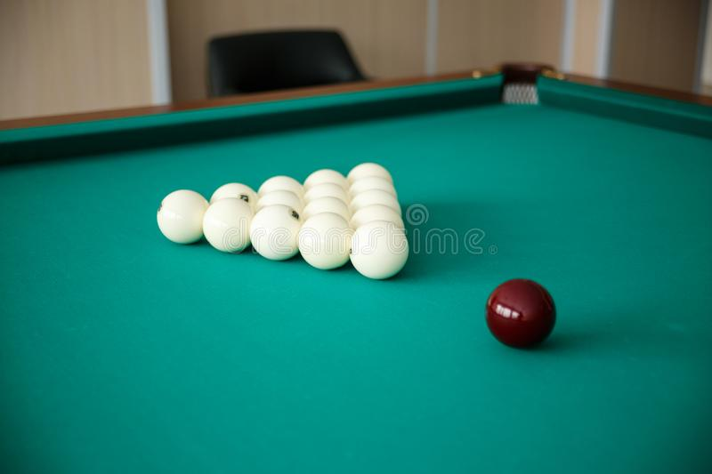 Cue ball for Russian billiards on the table. White billiard balls on the background. Green cloth. Selective focus royalty free stock photography