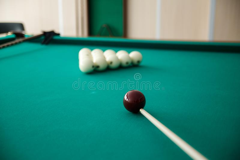Cue ball for Russian billiards on the table. White billiard balls on the background. Green cloth. Selective focus stock image