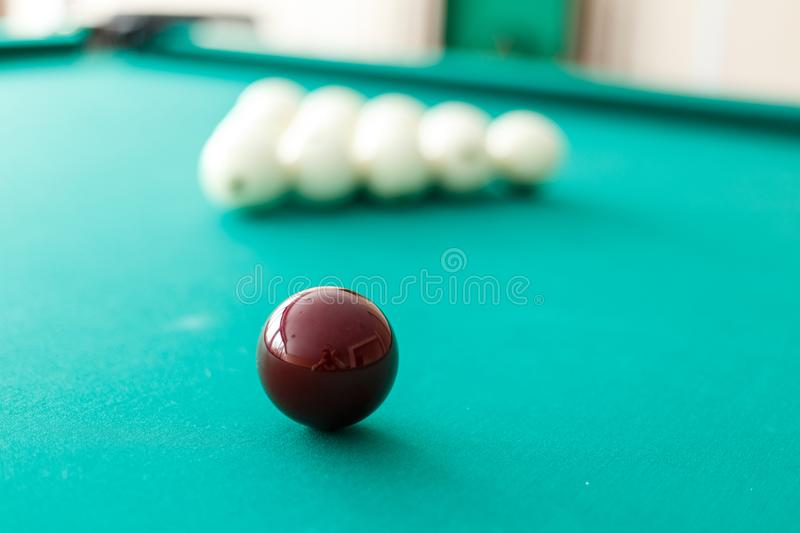 Cue ball for Russian billiards on the table. White billiard balls on the background. Green cloth. Selective focus stock images