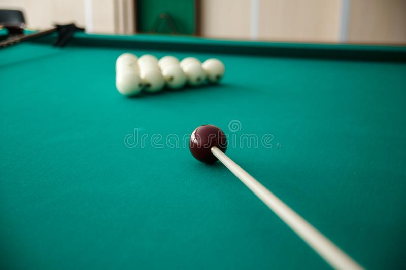 Cue ball for Russian billiards on the table. White billiard balls on the background. Green cloth. Selective focus stock photo