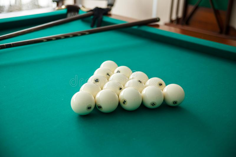 Cue ball for Russian billiards on the table. White billiard balls on the background. Green cloth. Selective focus royalty free stock image