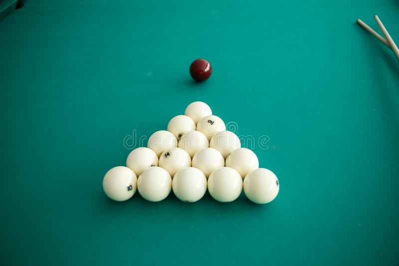 Cue ball for Russian billiards on the table. White billiard balls on the background. Green cloth. Selective focus royalty free stock photo