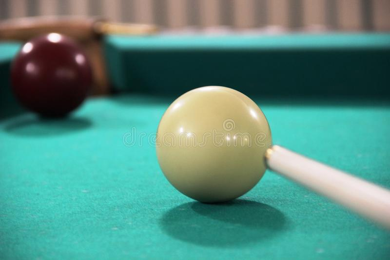 Cue, two billiard balls on a green cloth table, cue ball and white ball. Russian Billiards. Cue, two billiard balls on a green cloth table, cue ball and white stock photos
