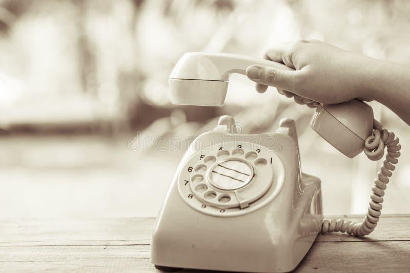 Cueillez à la main vers le haut du vieux téléphone de jour ou du téléphone rotatoire images stock