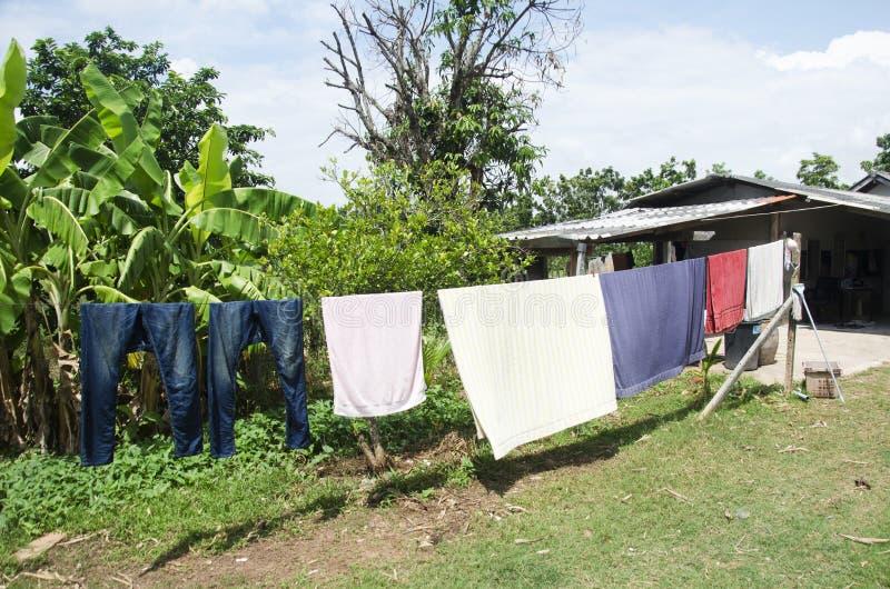 Cuelgue la ropa en la cuerda para tender la ropa después de lavarse para la ropa seca adentro foto de archivo libre de regalías