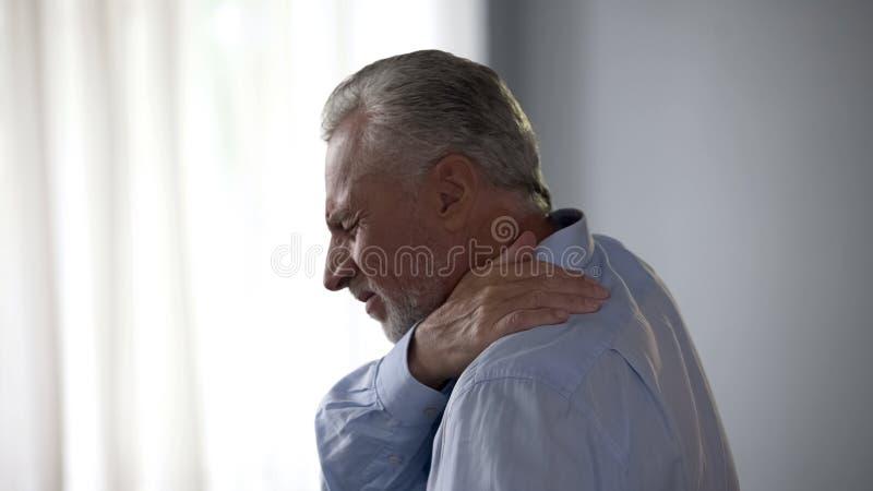 Cuello conmovedor masculino mayor en el dolor agudo que se coloca de lado, dolor en espina dorsal, salud fotos de archivo libres de regalías