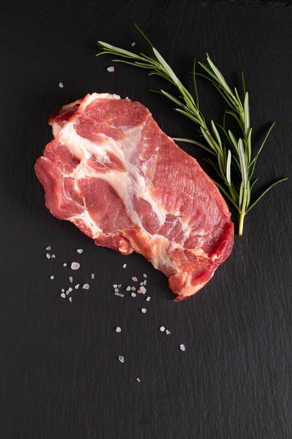 Cuello crudo fresco org?nico del cerdo de la comida en piedra negra de la pizarra con el espacio de la copia foto de archivo libre de regalías