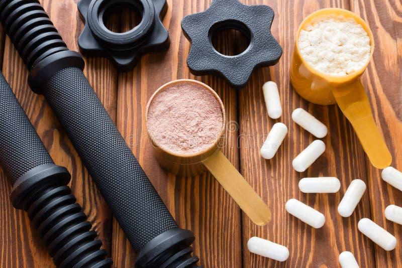 Cuello de la pesa de gimnasia y cucharas dosificadoras con la proteína foto de archivo libre de regalías