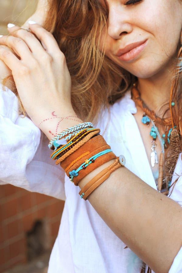 Cuello y manos femeninos con muchas pulseras del boho, collar de cuero y pendientes con las plumas foto de archivo libre de regalías