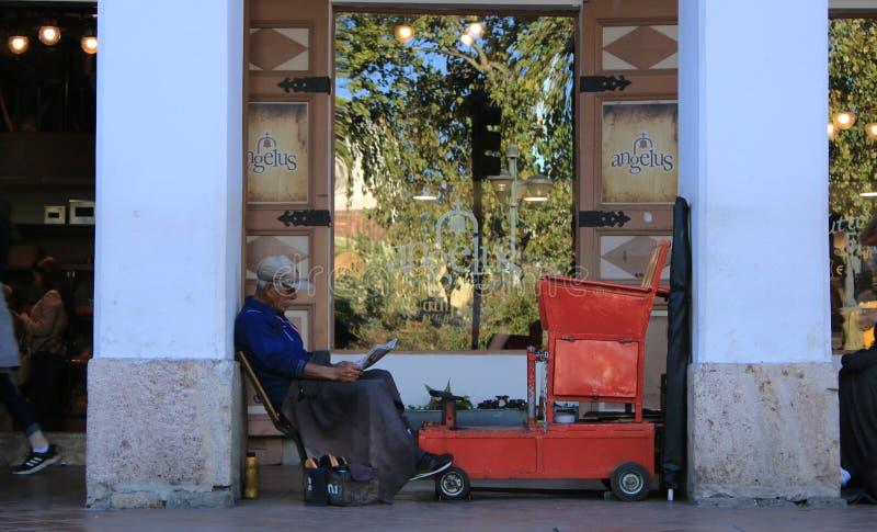 Cuenca - Ecuador, 2-5-2019: Gamal man som läser tidningen, medan vänta på en kund att göra ren skor royaltyfri fotografi