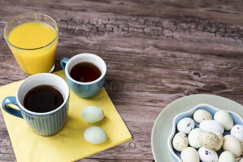 Cuenco azul con los huevos de Pascua en colores pastel, en la tabla de madera imagenes de archivo