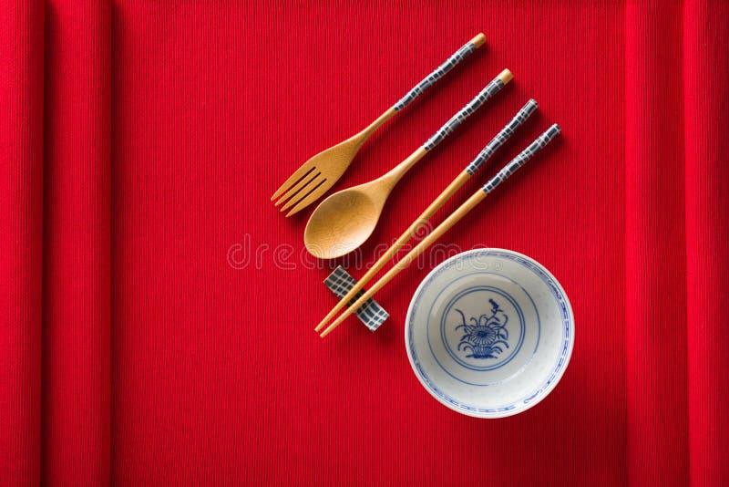 Cuenco, bifurcación, cuchara y palillos chinos en la estera roja fotografía de archivo libre de regalías