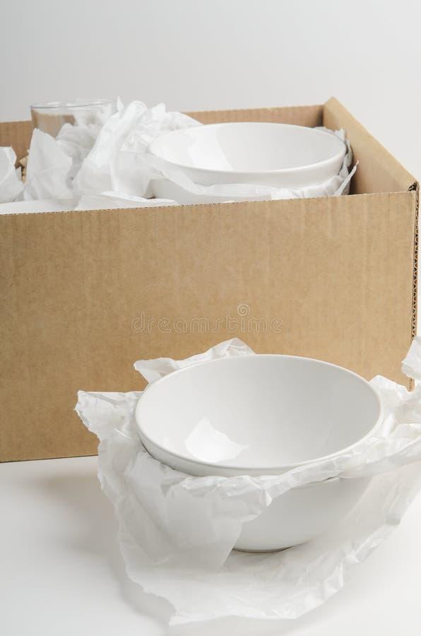Cuenco blanco en un fondo blanco con la caja de cartón en el paquete Relocalización del concepto, nuevos platos imágenes de archivo libres de regalías