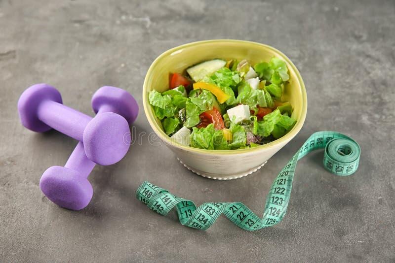 Cuenco con la ensalada vegetal, pesas de gimnasia y la cinta métrica en la tabla Adiete el alimento imagen de archivo