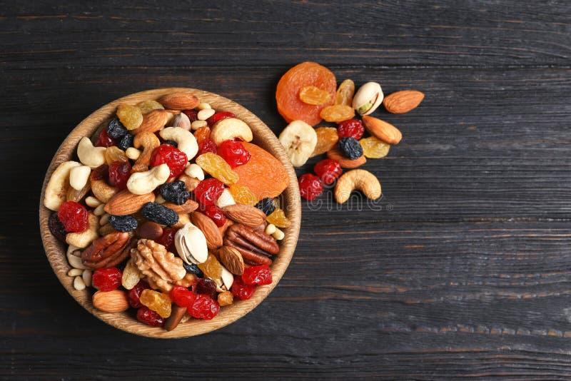Cuenco con las diversas frutas y nueces secadas en la tabla, visión superior fotografía de archivo
