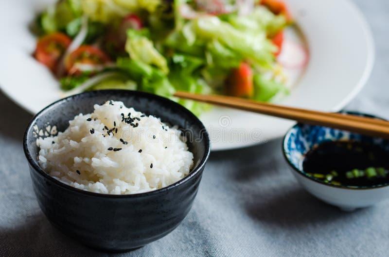 Cuenco de arroz con la salsa y las verduras de soja en el fondo imagenes de archivo