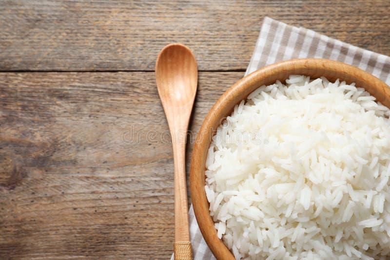 Cuenco de arroz delicioso en la tabla de madera, visión superior foto de archivo