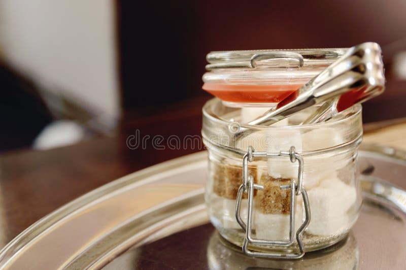 Cuenco de azúcar de cristal con el azúcar refinado en una tabla en un café Accesorios modernos para la comida imagenes de archivo