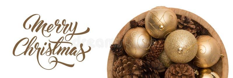 Cuenco de baubbles de oro de la Navidad y de conos del pino aislados sobre el fondo blanco La Navidad de oro adorna la bandera foto de archivo