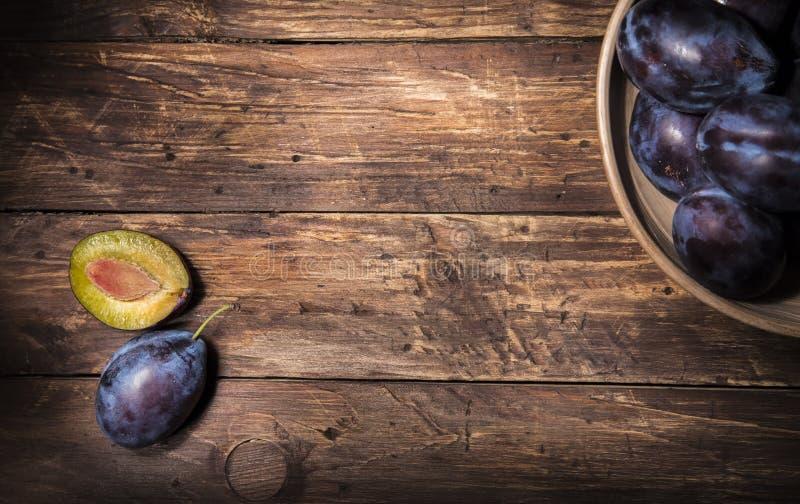 Cuenco de cerámica con los ciruelos y un solo ciruelo y una mitad del ciruelo con la piedra sobre el tablero de madera oscuro Fon fotografía de archivo