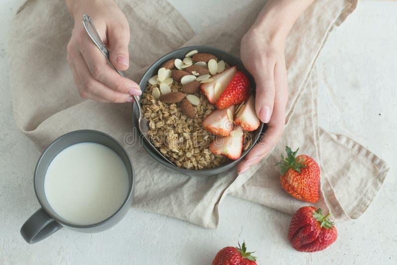 Cuenco de cerámica gris del desayuno sano con el granola, la fresa y las nueces en manos del ` s de la mujer Dieta y concepto de  foto de archivo